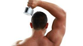 Гантель мышечного культуриста поднимаясь над его головой видеоматериал