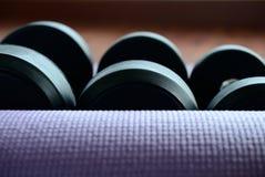 Гантель на циновке йоги Стоковое Изображение