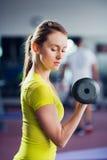 Гантель подходящей женщины детенышей поднимаясь в спортзале Стоковое Изображение