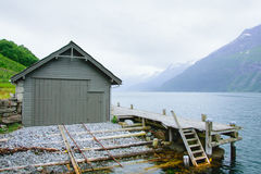 Гараж для шлюпок на береге фьорда с скалистыми берегами Стоковые Изображения