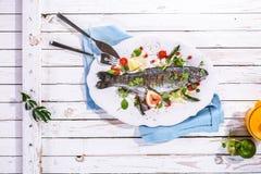 Гарнированные зажаренные рыбы на диске на деревенской таблице Стоковая Фотография