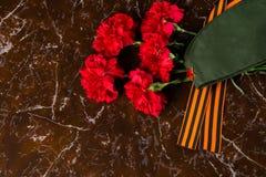 гвоздики, воинская крышка и лента St. George, на фоне мрамора Стоковое Изображение