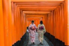 2 гейши среди красного деревянного строба торусов на святыне i Fushimi Inari Стоковые Фотографии RF