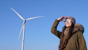 Генераторы энергии ветра, восторженные женщины в eyeglasses вытаращить в расстояние на предпосылке ветрянки сток-видео