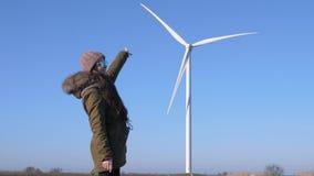 Генераторы энергии ветра, длинн-с волосами девушка с стеклами показывают палец на ветрянке на предпосылке неба сток-видео