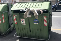 ГЕНУЯ, ИТАЛИЯ - 9-ое июня 2017 - переселенец ища еду внутри контейнера погани отброса Стоковые Фото