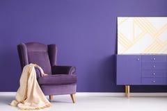 Геометрическая картина на фиолетовом шкафе в элегантной живущей комнате внутри стоковое изображение rf