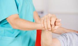 Гериатрическая медсестра держа руки старшего человека Стоковые Фото