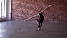 Гибкая девушка в черном bodysuit делает гимнастический прыжок кувырком в тренируя студии с предпосылкой кирпичной стены, медленно акции видеоматериалы