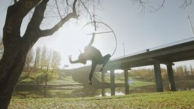 Гибкая женщина гимнастики выполняет фокусы акробатики на воздушном обруче outdoors видеоматериал