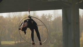 Гибкий брюнет с босыми ногами вися в кольце для воздушной акробатики в slo-mo сток-видео