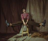 Гибкий парень сидел на шпагате на стуле Стоковая Фотография RF