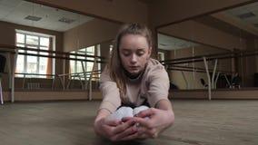 Гибкий танцор молодой женщины протягивая ноги в студии сток-видео