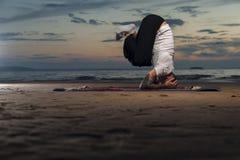 Гибкий человек йоги делая головную стойку на пляже Стоковое фото RF