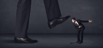 Гигантская персона шагая на концепцию маленького бизнесмена Стоковая Фотография