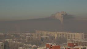 Гигантская печная труба фабрики испускает дым над городом зимы, загрязняет воздух и угрожает здоровье людей акции видеоматериалы