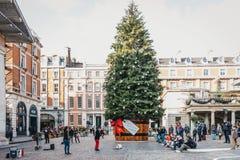 Гигантская рождественская елка в баке с биркой подарка перед рынком Ковент Гардена, Лондоном, Великобританией стоковое изображение rf
