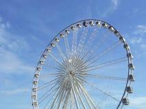 Гигантское колесо обеспечивает езды для осматривать облака города белые в голубом небе в предпосылке Стоковая Фотография