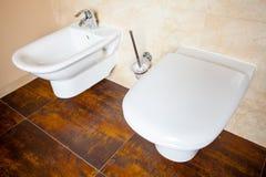 Гигиена. Белые биде и туалет фарфора. Интерьер ванной комнаты. Стоковое Фото