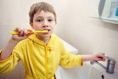 гигиена личная Забота ротовой полости мальчик чистит зубы щеткой стоковые фото