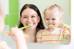 Гигиена Счастливые зубы матери и ребенка чистя щеткой Стоковое Изображение RF