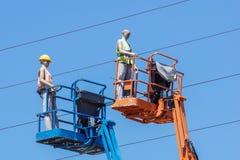 Гидравлическая передвижная платформа конструкции повышенная к голубому небу с ложными рабочий-строителями Думмичный человек Стоковые Изображения RF