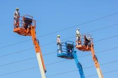 Гидравлическая передвижная платформа конструкции повышенная к голубому небу с ложными рабочий-строителями Думмичный человек Стоковые Фотографии RF