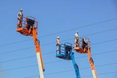 Гидравлическая передвижная платформа конструкции повышенная к голубому небу с ложными рабочий-строителями Думмичный человек Стоковое Изображение