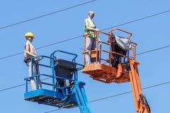 Гидравлическая передвижная платформа конструкции повышенная к голубому небу с ложными рабочий-строителями Думмичный человек Стоковая Фотография RF