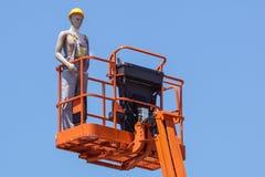 Гидравлическая передвижная платформа конструкции повышенная к голубому небу с ложными рабочий-строителями Думмичный человек Стоковое Изображение RF