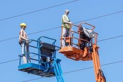 Гидравлическая передвижная платформа конструкции повышенная к голубому небу с ложными рабочий-строителями Думмичный человек Стоковое Фото
