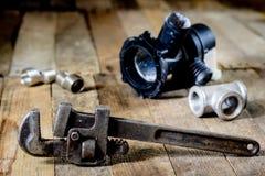 Гидротехник, инструменты для водопроводчика на деревянном столе Мастерская, ставит a на обсуждение стоковое фото
