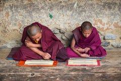 2 гималайских бутанских молодых монаха послушника сидя на поле и chanting, Бутан стоковая фотография
