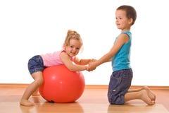 гимнастика мальчика ее преподавательство маленькой сестры стоковое изображение rf