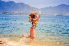 Гимнаст блондинкы тонкий в бикини бежит в море против холмов Стоковые Фото