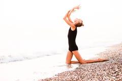 Гимнаст в красивом представлении на фоне океана стоковые фотографии rf
