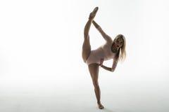 Гимнаст молодой женщины протягивая ноги на белой предпосылке Стоковое фото RF