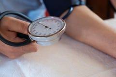 Гипертенсивный пациент выполняя испытание кровяного давления автоматическое/человека стоковая фотография rf
