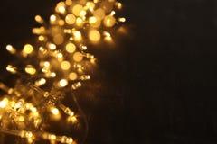 Гирлянда золота рождества теплая освещает на задней деревянной предпосылке верхний слой яркого блеска Стоковое Фото
