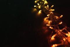 Гирлянда золота рождества теплая освещает на задней деревянной предпосылке верхний слой яркого блеска Стоковые Фотографии RF