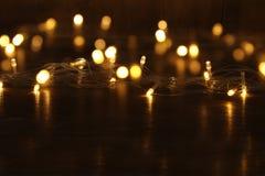 Гирлянда золота рождества теплая освещает на задней деревянной предпосылке Стоковая Фотография