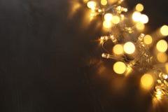 Гирлянда золота рождества теплая освещает на задней деревянной предпосылке верхний слой яркого блеска Стоковые Изображения RF
