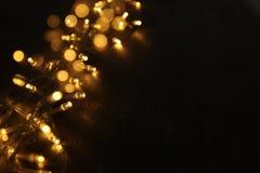 Гирлянда золота рождества теплая освещает на задней деревянной предпосылке верхний слой яркого блеска Стоковое Изображение RF