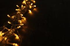 Гирлянда золота рождества теплая освещает на задней деревянной предпосылке Стоковое Фото