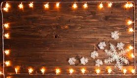 Гирлянда золота рождества теплая освещает с снежинками на деревянной деревенской предпосылке Концепция рождества или Нового Года Стоковая Фотография