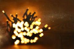 гирлянда яркого блеска освещает предпосылку черное золото де-сфокусированный стоковые фото