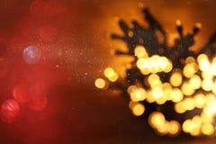 гирлянда яркого блеска освещает предпосылку черное золото де-сфокусированный стоковое изображение