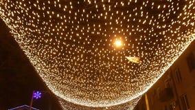 Гирлянды рождества светящие в улицах города ночи сток-видео