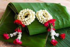 Гирлянда жасмина цветков на предпосылке лист банана Стоковое Изображение RF