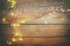Гирлянда золота рождества освещает на деревянной деревенской предпосылке Стоковые Изображения RF